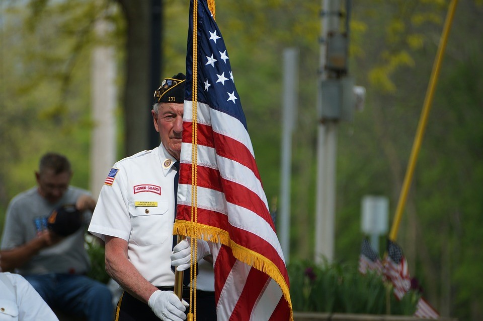 Old U.S Veteran with the US Flag | Goodwill Car Donations