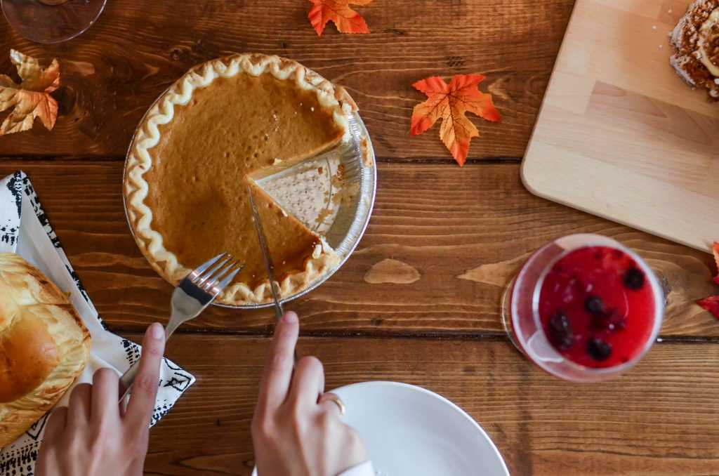 Person Holding Table Knife About to Slice some Pumpkin Pie | Goodwill Car Donation