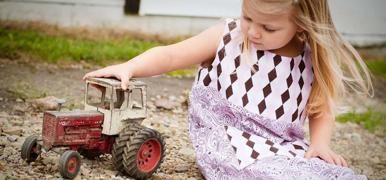 Little Girl Playing a Tractor Toy | Goodwill Car Donations