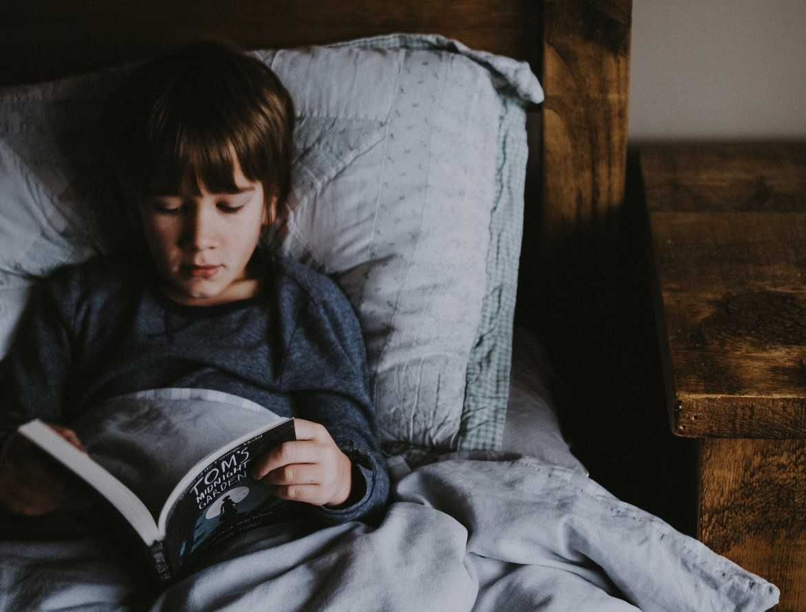 Kid Reading in Bed | Goodwill Car Donations