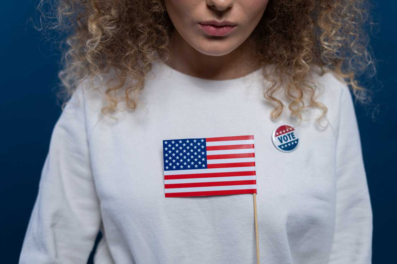 Woman with American Flag and Vote Pin   Goodwill Car Donations