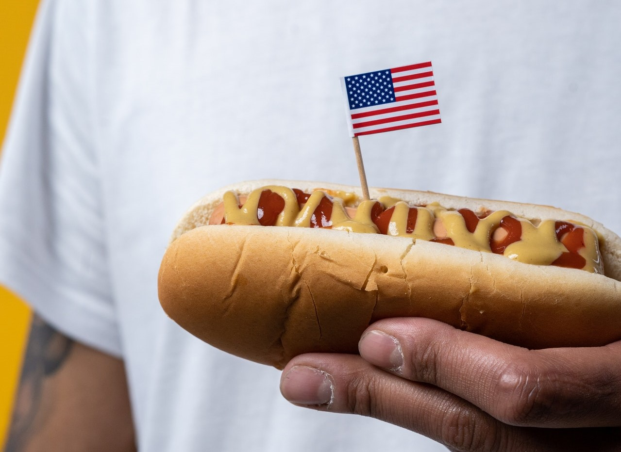 Person Holding a Hotdog with the US Flag | Goodwill Car Donations