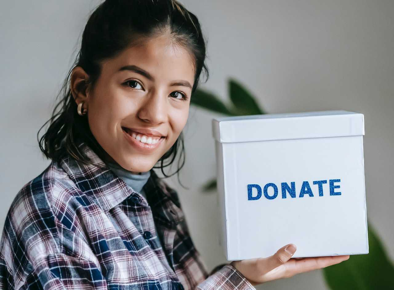 Woman Smiling Holding Box for Donation | Goodwill Car Donations